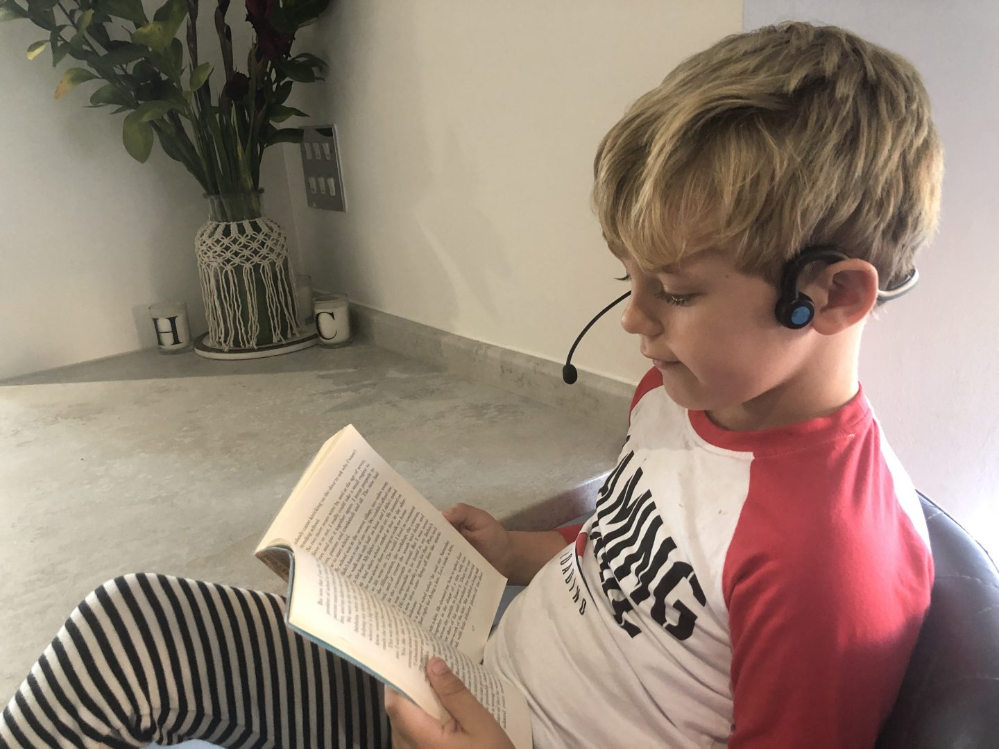 Harry reading a book and using the Forbrain Multisensory Headset